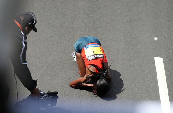Rita Jeptoo, the Women's Elite winner of the 118th Boston Marathon drops to the ground, overcome with emotion after she took first place and set a course record (2:18:57) on Monday morning. DAVID LE/Staff photo 4/21/14
