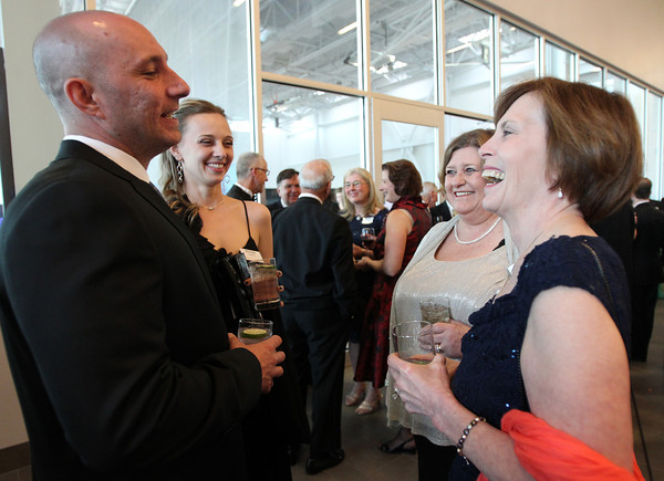 "Salem State University President Dr. Patricia Maguire Meservey, right, laughs while chatting with Phil and Nicole Lippens, left, and Mary DeChillo, second from right, during a gala held in the atrium of the Gassett Fitness Center on Saturday evening. The university announced the public phase of a $25 million campaign, the largest fundraising initiative ever taken by the university, and announced that they've already raised $15 million towards the goal in a private phase of the campaign, which they called ""10,000 reasons."" DAVID LE/Staff photo. 4/12/14"