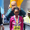 Rita Jeptoo, winner of the Women's Elite Boston Marathon race smiles as Governor Deval Patrick places the winner's gold olive wreath on her head. DAVID LE/Staff photo 4/21/14