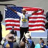 Meb Keflezighi, the 118th Boston Marathon Men's Elite champion holds his arms wide with an American flag stretched between them on Monday morning. DAVID LE/Staff photo 4/21/14