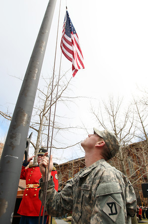 Specialist Joshua Lacorse, of the 101st Engineer Battalion, lowers the American flag to half mast as Lt. Col. Larry Conway, Commander of the Second Corps Cadets Veterans Association of Salem, left, salutes during a ceremony at Armory Park as part of the 377th Anniversary of the First Muster on Salem Common. DAVID LE/Staff photo 4/5/14