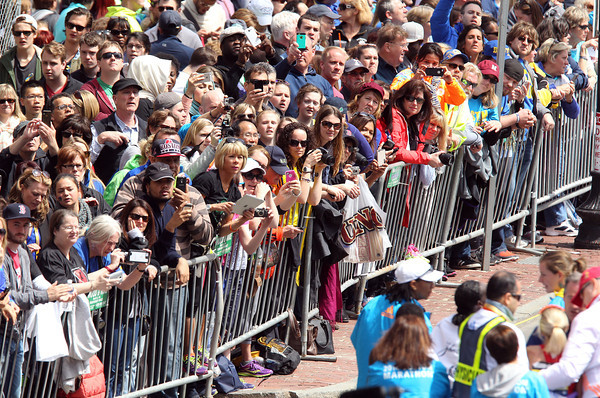 Thousands of fans yell messages of support and encouragement to Marblehead native Shalane Flanagan as she is helped to the medical tent after finishing the 118th Boston Marathon in 7th place on Monday morning. DAVID LE/Staff photo 4/21/14