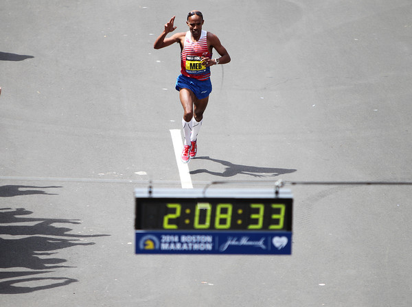 Meb Keflezighi, the 118th Boston Marathon Men's Elite champion acknowledges thousands of screaming fans as he bears down on the clock and finish line as he cruises to a win in the 118th Boston Marathon. DAVID LE/Staff photo 4/21/14