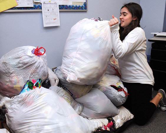 KEN YUSZKUS/Staff photo.  8th grade student Julie Natale at the Holten Richmond Middle School in Danvers moves one of the bags containing clothing which was donated to the school during a clothing drive to benefit Cradle to Crayons, a nonprofit organization that gives the clothing and school supplies to low income families.  4/10/14