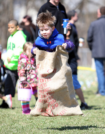 Christopher Coughlin, 6, of Manchester, leaps through the air during a sack race at Netcast's 4th annual Easter Egg Hunt held at Beverly High School on Saturday morning. DAVID LE/Staff photo. 4/19/14