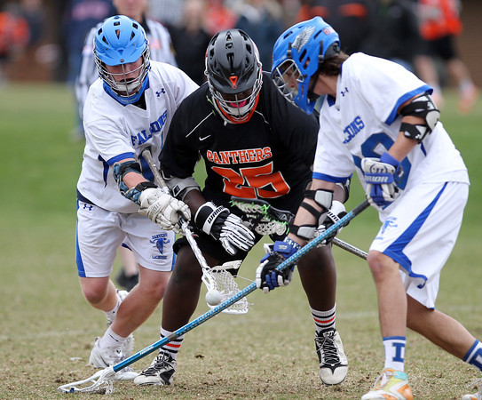 Beverly's Rick McFarland (25) battles for a loose ball with Danvers midfielder Matt Flynn (1) and defense Anthony Serino (20) during the second quarter of play on Monday afternoon. DAVID LE/Staff Photo. 4/28/14