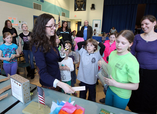 Ward Two City Councilor Heather Famico hands out the third place prize in the recycled art competition on Thursday evening. The Carlton School hosted its 3rd Annual Earth Day Fest in the cafeteria on Thursday evening. In addition to crafts and games, Ward Two Councilor Heather Famico and Ward Six Councilor Beth Gerard served as two judges for a recycled art competition and Whole Foods Market and Mass Auduban set up table to share some information with the students. DAVID LE/Staff photo. 4/17/14