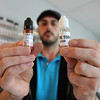 Alan Kelleher, owner of North Shore Vapors, on Highland Ave in Salem, holds up two bottles of refill liquids used in e-cigarettes, one with a warning label, and one without. There has been recent talk that the FDA would mandate warning labels on the liquid refill bottles, however Kelleher says it could take up to two-years to pass. DAVID LE/Staff photo. 4/28/14