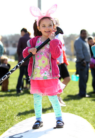 Four-year-old Ava Hartley, of Marblehead, laughs while pretending to paddle board at the Surfari Stand Up Paddle and Surf table during Netcast's 4th annual Easter Egg Hunt held at Beverly High School on Saturday morning. DAVID LE/Staff photo. 4/19/14
