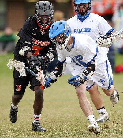 Danvers midfielder Stephen Ganley (15) loses control of the ball after it gets chopped out of his grasp by Beverly midfielder Peter Mulumba (7) during the third quarter of play on Monday afternoon. DAVID LE/Staff Photo. 4/28/14