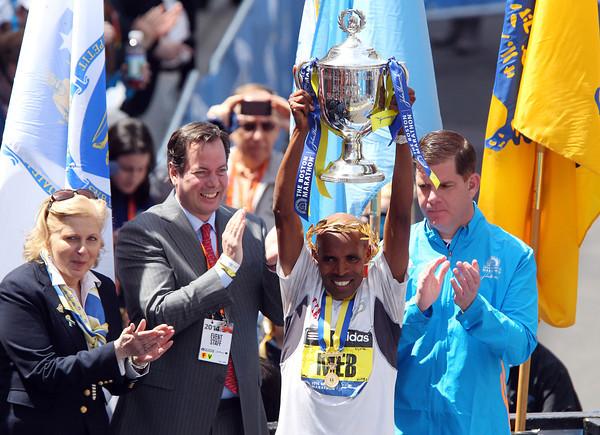 Meb Keflezighi, the 118th Boston Marathon Men's Elite champion hoists the championship trophy high over his head. DAVID LE/Staff photo 4/21/14