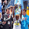 Meb Keflezighi, the 118th Boston Marathon Men's Elite champion hoists the championship trophy high over his head. DAVID LE/Staff photo 4/21/14