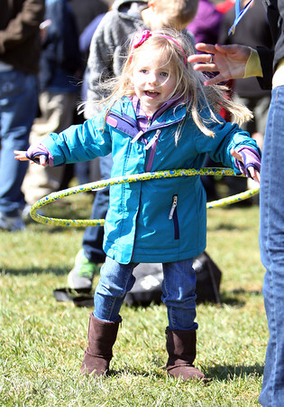 Evie Crowell, 4, of Beverly, smiles while hula-hooping during Netcast's 4th annual Easter Egg Hunt held at Beverly High School on Saturday morning. DAVID LE/Staff photo. 4/19/14