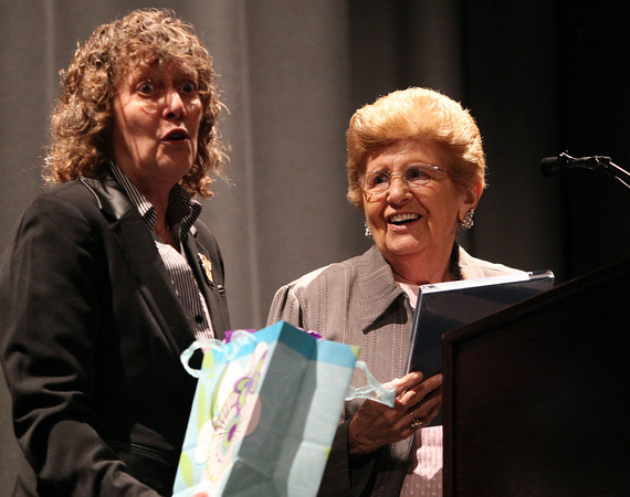 Rena Finder, right, smiles as she is presented with a few gifts for winning the Holocaust Center Service Award by Sandy Weitz, left, during Yom HaShoah 2014 held in the auditorium at Peabody Veterans Memorial High School on Monday evening. DAVID LE/Staff Photo. 4/28/14