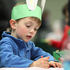 Four-year-old Gavin Bolduc, of Beverly, sports a set of bunny ears while coloring during a Spring Celebration event held in the Field House at Endicott College on Wednesday afternoon. DAVID LE/Staff photo. 4/16/14