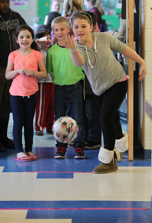 Carlton School fifth grader Paige Foster, 11, right, bowls a ball towards pins made of recycled plastic bottles and sand as first grader Kaelyn Eaton, 7, left, and fourth grader Alex Reid, 10, center, look on anxiously. The Carlton School hosted its 3rd Annual Earth Day Fest in the cafeteria on Thursday evening. In addition to crafts and games, Ward Two Councilor Heather Famico and Ward Six Councilor Beth Gerard served as two judges for a recycled art competition and Whole Foods Market and Mass Auduban set up table to share some information with the students. DAVID LE/Staff photo. 4/17/14