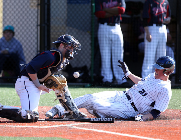 Central Catholic catcher Jon Parsons, left, cannot corral a throw to home plate as St. John's Prep junior Ted McNamara (21) slides in safely. The Raiders fell to the Eagles 9-3 at St. John's Prep in Danvers on Thursday afternoon. DAVID LE/Staff photo 4/10/14