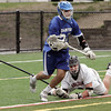KEN YUSZKUS/Staff photo.  Danvers' Trevor Chasse gets away as Marblehead's Liam Gillis falls near the net during the Danvers at Marblehead boys lacrosse game. 4/23/14