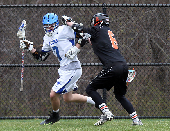 Danvers attack Troy Fleming (7) wards off a check from Beverly defense Sam Traicoff (6) during the first quarter of play on Monday afternoon. DAVID LE/Staff Photo. 4/28/14