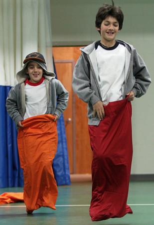 Brothers Abel, 7, left, and Jaime Alarcon, 11, of Beverly, race each other in a potato sack race for an Easter Treat during a Spring Celebration event held in the Field House at Endicott College on Wednesday afternoon. DAVID LE/Staff photo. 4/16/14