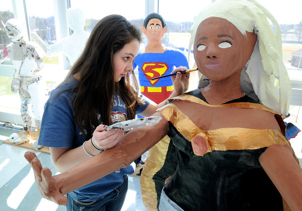 KEN YUSZKUS/Staff photo. Nora Chan paints the sculpture of Storm from the Xmen. The 8th grade art class students at the Holten Richmond Middle School in Danvers built the large various sculptures while in small groups.  4/10/14