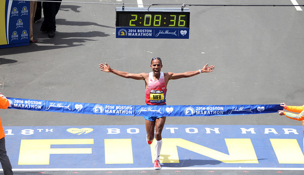 Meb Keflezighi, the 118th Boston Marathon Men's Elite champion holds his arms wide and lets out a shout of excitement and exhilaration as he crosses the finish line on Monday morning. DAVID LE/Staff photo 4/21/14