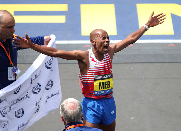Meb Keflezighi, the 118th Boston Marathon Men's Elite champion holds his arms wide and lets out a shout of excitement and exhilaration after he became the first American man to win the Marathon since 1983 on Monday morning. DAVID LE/Staff photo 4/21/14