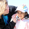 Five-year-old Nikki Pillai, of Hamilton, smiles while getting her face painted by volunteer Erica Lee, of Beverly, during Netcast's 4th annual Easter Egg Hunt held at Beverly High School on Saturday morning. DAVID LE/Staff photo. 4/19/14