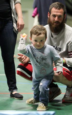 Brayden Fullerton, 2, of Beverly, carefully lines up an egg toss under the watchful eye of his father Jason, right, during a Spring Celebration event held in the Field House at Endicott College on Wednesday afternoon. DAVID LE/Staff photo. 4/16/14