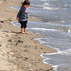 KEN YUSZKUS/Staff photo. Rose Alpuerto, 3, of Peabody walks barefoot near the waves lapping the shoreline of Dane Street Beach in Beverly Monday morning.