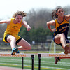Bishop Fenwick senior Samantha Keiran, left, and St. Mary's junior Carmel Lozzi, right, leap over the final hurdle and sprint towards the finish line in the 110 high hurdles on Tuesday morning at Bishop Fenwick High School in Peabody. DAVID LE/Staff photo. 4/22/14