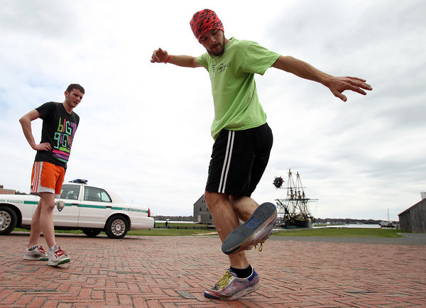 Nick Polini, of Pennsylvania, right, visiting his friend Kevin Hogan, of Beverly, kicks up a Hacky Sack behind him while playing in front of the Friendship in downtown Salem on Monday afternoon. DAVID LE/Staff photo. 4/28/14