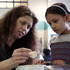 Ward Six City Councilor Beth Gerard, left, shows various pieces of honeycomb wax to Carlton School kindergartener Nira Schumaker, 5, during the 3rd Annual Earth Day Fest in the Carlton school cafeteria on Thursday evening. In addition to crafts and games, Ward Two Councilor Heather Famico and Ward Six Councilor Beth Gerard served as two judges for a recycled art competition and Whole Foods Market and Mass Auduban set up table to share some information with the students. DAVID LE/Staff photo. 4/17/14