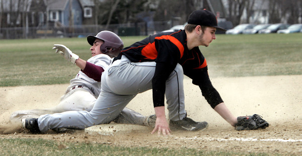 KEN YUSZKUS/Staff photo. Beverly's George Hillios stops Lynn English 2 player who is out at 3rd at the Lynn English at Beverly High School baseball game.