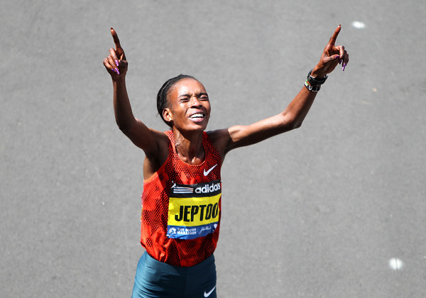 Kenyan Rita Jeptoo, points skywards after crossing the finish line of the 118th Boston Marathon. DAVID LE/Staff photo 4/21/14