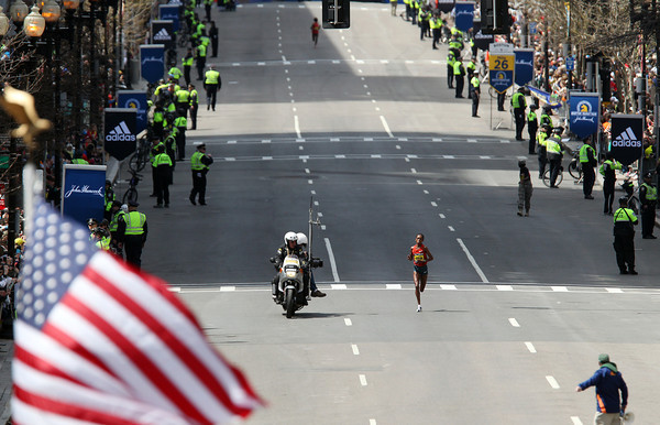 Rita Jeptoo, of Kenya, accompanied by a police escort and cheers of thousands of spectators crowded along Boylston Street, sprints towards the finish line of the 118th Boston Marathon in a course record time of 2:18:57 and first place finish on Monday morning. DAVID LE/Staff photo 4/21/14