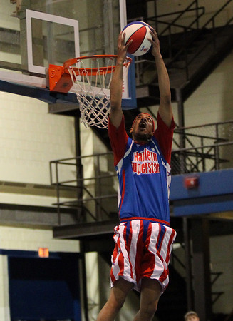 Harlem Superstar Skyscraper throws down a reverse dunk during a game against the Peabody Firefighters team at Peabody Veterans Memorial High School on Saturday afternoon. DAVID LE/Staff photo. 4/19/14