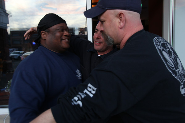 The Salem Waterfront Hotel has offered free rooms for any firefighters coming from around the country to Massachusetts for the funerals of Boston Firefighters Lt. Edward J. Walsh and Firefighter Michael R. Kennedy. Phil Lesley, left, of Cleveland, Ohio, gets a warm welcome and hug from Iggy McSorley, of Fort Lauderdale, center, and Bob Welch, from the Manchester Fire Department upon his arrival to the Salem Waterfront Hotel on Tuesday evening. DAVID LE/Staff photo 4/1/14