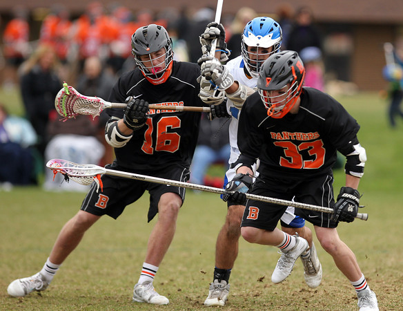 Beverly senior Zach Duguid (16) tries to hold off Danvers midfielder Anthony Scarfo (12) as he tries to dislodge the ball from Beverly junior Bryan Flaherty's (33) stick on Monday afternoon. DAVID LE/Staff Photo. 4/28/14