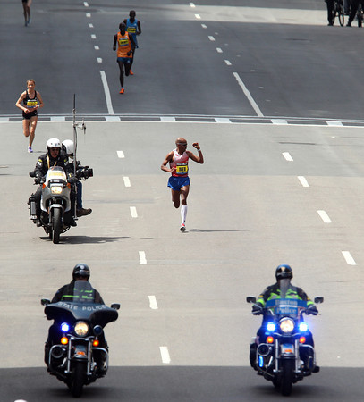 Meb Keflezighi pumps his fist as he cruises towards a first place finish, the first American marathoner to win the Boston Marathon since 1983, during the 118th Boston Marathon. DAVID LE/Staff photo 4/21/14