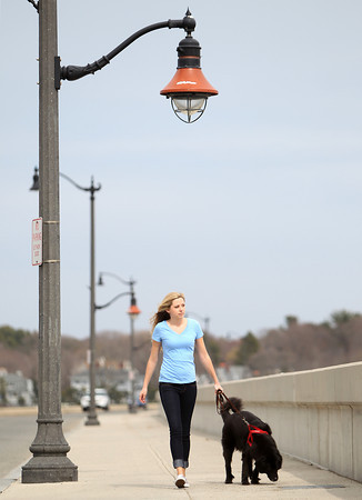 Sarah Wheeler, 22, of Marblehead, walks her dog Guiness along the Causeway on a windy Tuesday afternoon. DAVID LE/Staff photo. 4/22/14