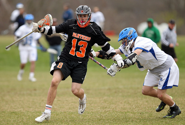 Beverly attack Graham Doherty (13) escapes a check from Danvers attack Troy Fleming (7) on Monday afternoon. DAVID LE/Staff Photo. 4/28/14