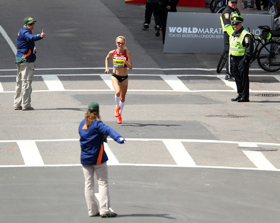 Race volunteers point the way to the finish line for Marblehead native Shalane Flanagan as she sprints down the home stretch down Boylston Street on Monday morning. DAVID LE/Staff photo 4/20/14
