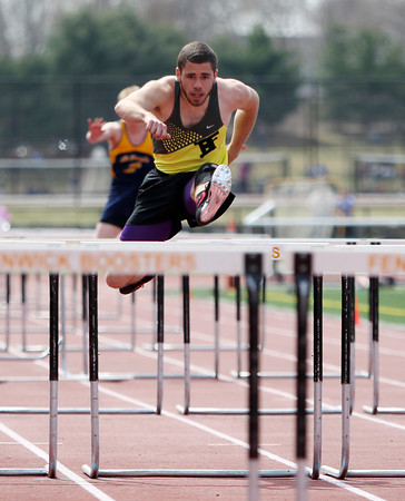 Bishop Fenwick senior Nick Tambini flies over a hurdle in the 100m high hurdles during a dual meet against St. Mary's (Lynn) and Cathedral on Tuesday morning at Bishop Fenwick High School in Peabody. DAVID LE/Staff photo. 4/22/14