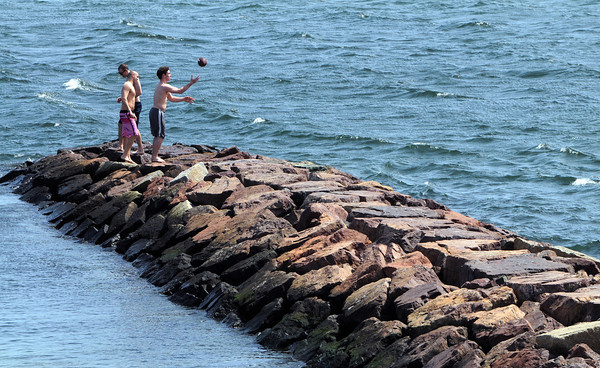 KEN YUSZKUS/Staff photo. From left, friends Dillon Coleman, Zach Caldwell, both of Beverly, and Matthew Warner of Westford walk along the rock jetty at Independence Park in Beverly on a warm Monday afternoon.