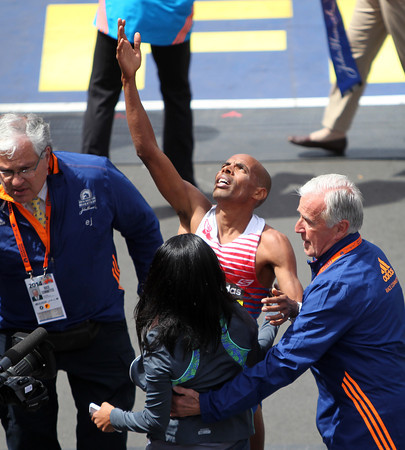 Meb Keflezighi, the 118th Boston Marathon Men's Elite champion holds his arms skyward as he is greeted by his wife Yordanos after he crossed the finish line on Monday morning. DAVID LE/Staff photo 4/21/14