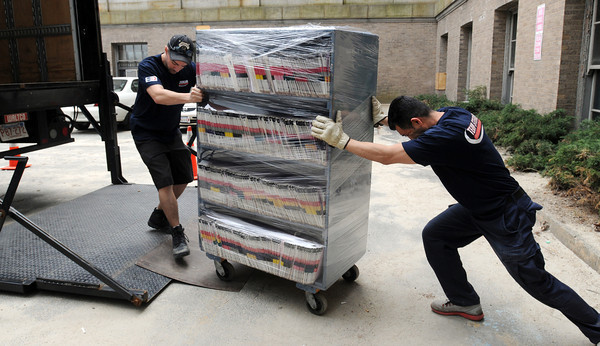 KEN YUSZKUS/Staff photo.  Tom Pike, left, and Fernando Colon roll a container full of files from the Essex Probate & Family Court into a truck to be transported to Shetland Park in Salem.  4/22/14