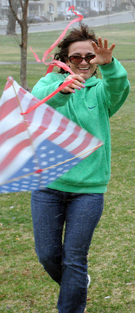 KEN YUSZKUS/Staff photo. The kite was immediately demolished by the strong wind coming off Salem Harbor as Kim Casey of Beverly lets go of the kite. She and her friends braved the wind driven rain to fly the kite Tuesday afternoon in Beverly.
