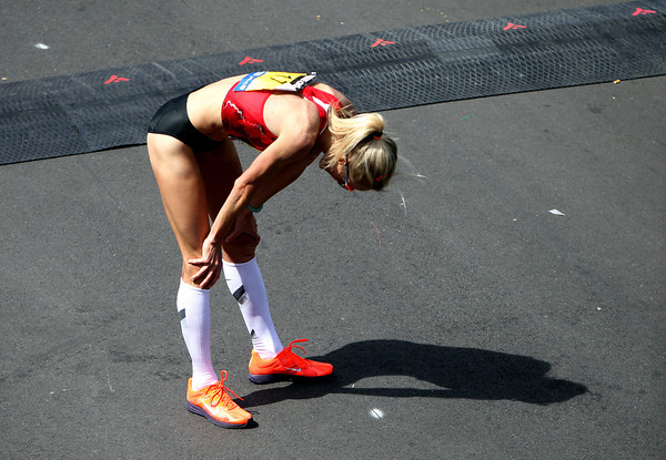 Marblehead native Shalane Flanagan puts her hands on her knees in exhaustion after completing the 118th Boston Marathon in 7th place in a PR time of 2:22:02 on Monday morning. DAVID LE/Staff photo 4/21/14