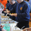 KEN YUSZKUS/Staff photo. Jim Kimber, right, of Engine 5 of the Peabody Fire Department digs into the breakfast buffet set up in the Wiggin Auditorium of Peabody City Hall. The breakfast was a fundraiser to benefit Aiden Dupont, who is 3 years old and battling a rare cancer of the eye. 4/16/14
